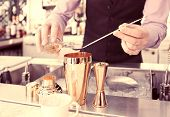 image of bartender  - Bartender is adding ingredient in shaker at bar counter - JPG