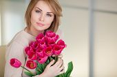 Постер, плакат: Happy woman with a bouquet of pink tulips