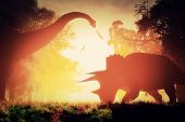 stock photo of mystique  - Dinosaurs in Prehistoric Jungle in the Sunset Sunrise 3D Artwork - JPG