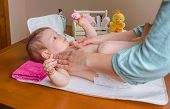 pic of diaper change  - Mother massaging body of adorable baby lying after the change of diaper
