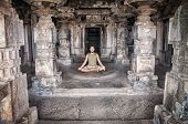 image of carving  - Man doing meditation in ancient temple with carving columns in Hampi Karnataka India - JPG
