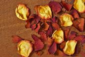 image of keepsake  - Various dried rose petals are pictured closeup on a textured piece of cut wood - JPG