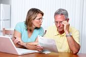 foto of senior adult  - Senior couple looking bills at home with computer - JPG