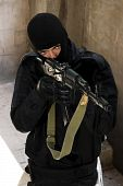 stock photo of extremist  - Gunman aiming his target with an automatic russian AK - JPG