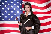pic of law-books  - Female Judge With A Law Book And A Wooden Gavel Standing In Front Of American Flag - JPG