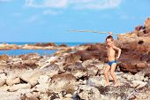 stock photo of aborigines  - cute boy with bamboo spear pretends like he is aborigine on desert island - JPG