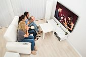 image of watching movie  - Multiethnic Young Women Sitting On Couch Watching Movie At Home - JPG
