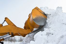 image of bulldozers  - A bulldozer clears snow drifts after the storm - JPG