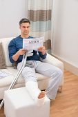 stock photo of crutch  - Disabled Man With Crutches Sitting On Sofa Reading Newspaper - JPG