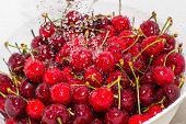 stock photo of freezing  - Freezed drops of water over the ripe cherries rinsed with water in the white colander - JPG