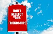stock photo of neglect  - Do Not Neglect Your Friendships motivational quote written on red road sign isolated over clear blue sky background - JPG