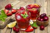pic of cold drink  - Cold strawberry and cherries drink with fresh strawberriescherries and lemon on wooden background - JPG