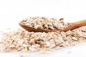 stock photo of whole-grain  - Whole grain rolled oats flakes with wooden spoon - JPG