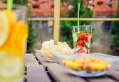 picture of infusion  - Infused fruit water cocktails and snacks bowls over a wooden table outdoors - JPG