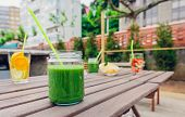 pic of infusion  - Green vegetable smoothies and infused fruit water cocktails over a wooden table outdoors - JPG