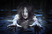 pic of bloody  - Beautiful witch woman dressed white bloody shirt standing in the river - JPG