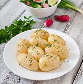 pic of boil  - Young boiled potatoes with butter and dill on a white plate - JPG