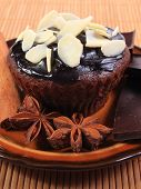 stock photo of chocolate muffin  - Homemade delicious fresh baked chocolate muffins with sliced almonds pieces of chocolate star anise and stick of cinnamon lying on plate - JPG