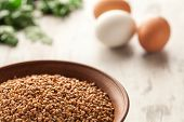 foto of ceramic bowl  - Composition with ceramic bowl dry buckwheat and eggs on background - JPG