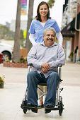 stock photo of wheelchair  - Carer Pushing Disabled Senior Man In Wheelchair - JPG