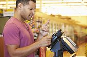stock photo of fingers crossed  - Hopeful Customer Paying For Shopping At Checkout With Card Crossing Fingers - JPG
