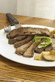 pic of flank steak  - Sliced juicy skirt steak with potatoes and arugula garnish - JPG
