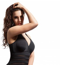 stock photo of monokini  - Brunette girl with wet hair in a black swimsuit on a white background isolated - JPG