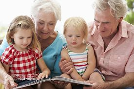 stock photo of grandparent child  - Grandparents And Grandchildren Reading Book On Garden Seat - JPG