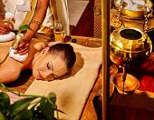Постер, плакат: Woman lie on stomach having ayurvedic massage with pouch of rice Shirodhara pot for head massage on