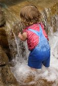 stock photo of wet pants  - toddler in overalls playing in waterfall - JPG