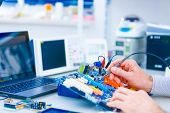 Repair motherboard in electronics laboratory. Technological background with closeup on tester checki poster
