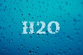 stock photo of h20  - a background made by droplets of water with blue tones and the word  - JPG