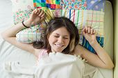 Good Morning, Teenage Girl Wakes Up And Smiles At The Camera Lying On A Pillow In Her Bed, Top View. poster