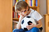Little Blond Preschool Kid Boy With Ball Watching Soccer Football Cup Game On Tv. Sad, Crying And De poster