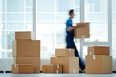 Blurred motion of contemporary worker with packed box walking to new office while delivering it to c poster