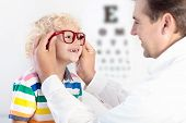 Child At Eye Sight Test. Little Kid Selecting Glasses At Optician Store. Eyesight Measurement For Sc poster