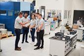 Engineering Team Meeting On Factory Floor Of Busy Workshop poster
