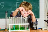 Little Kid Learning Chemistry In School Laboratory. Experimenting With Chemicals Little Boy At Chemi poster