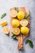Fresh Lemons In Wooden Bowl With  Leaves On Grey Stone  Background. Fresh Fruits And  Slice Flat Lay poster