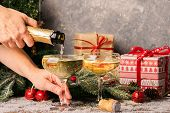 Woman Fills A Glass Of Champagne. Sparkling Wine In Elegant Glasses On A Christmas Table With Gifts  poster