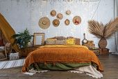 Beautiful Cozy Bedroom With Boho Style Interior, Pillows, Cushions, Green Plants In Flower Pot, Bed  poster