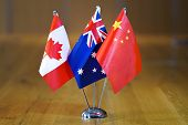 Three Flags On The Table. Flags Of Canada, Australia And China. Flags Of Canada, Australia And China poster