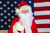 Santa Claus with American Flag. Santa stands in front of the American Flag Smiles and Points at You  poster