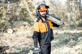 Portrait Of A Professional Lumberman In Protective Workwear With A Chainsaw And Wooden Logs During T poster