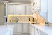 interior of neoclassical style white and gold wooden kitchen with island in luxury home poster