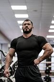 Strong Handsome Young Caucasian Man In Black Sportswear Indoor Gym Posing poster
