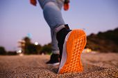 Girl Feet In Sneakers With Bright Orange Soles Go Away On The Sand. Concept For Start, Going, Step F poster