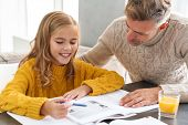 Cute smiling little girl doing homework with her dad while sitting at the table at the living room poster