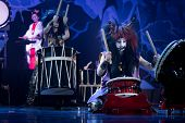 Traditional Japanese Performance. Taiko Drummers In A Wig And A Demon Mask Perform On Stage With Dru poster