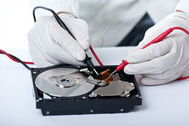 picture of ohm  - A technician repairing an hard disk with a tester - JPG